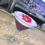 Red coloured cocktail with red coloured flower placed on bar